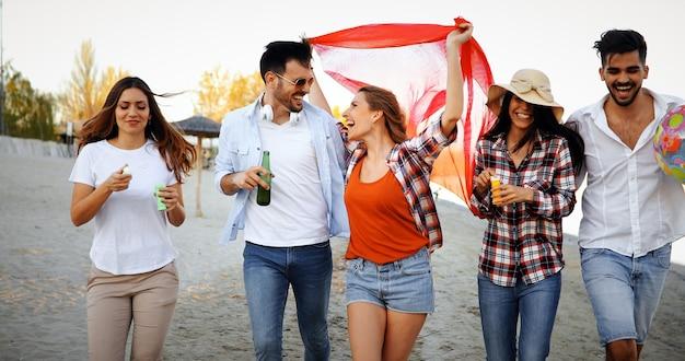 Grupo de amigos felizes festejando na praia e se divertindo
