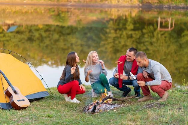 Grupo de amigos felizes fritando salsichas na fogueira perto do lago.