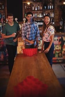 Grupo de amigos felizes jogando beer pong