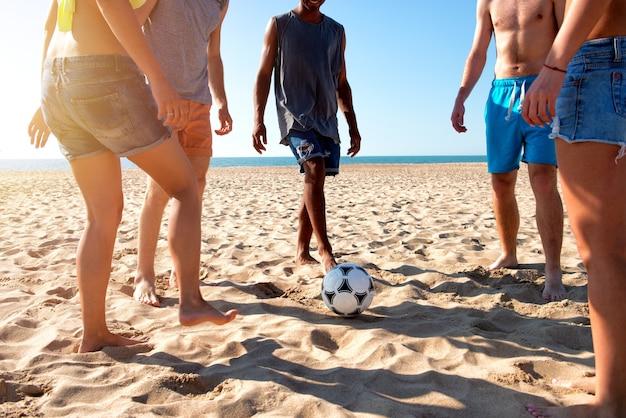 Grupo de amigos felizes jogando futebol na praia