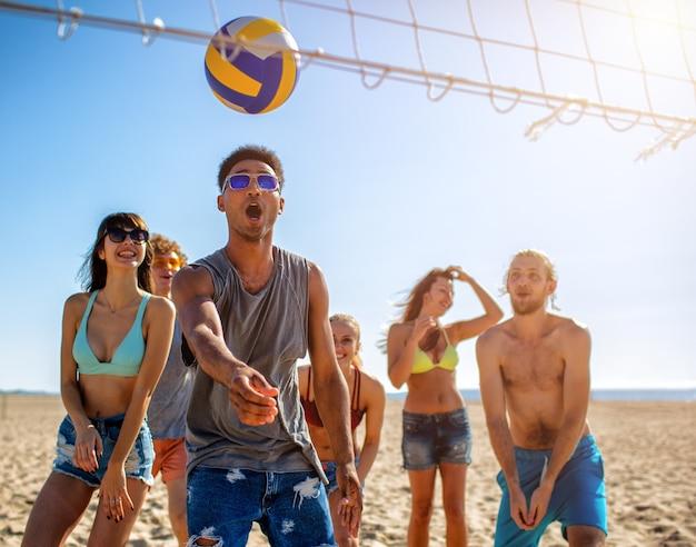Grupo de amigos felizes jogando vôlei de praia na praia
