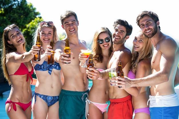 Grupo de amigos felizes mostrando garrafas de cerveja e um copo de coquetel