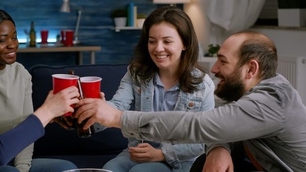 Grupo de amigos felizes multiculturais se divertindo durante a festa grátis do wekeend bebendo cerveja comendo lanche ...