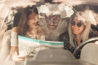 Grupo de amigos felizes olhando mapa sentado dentro do carro