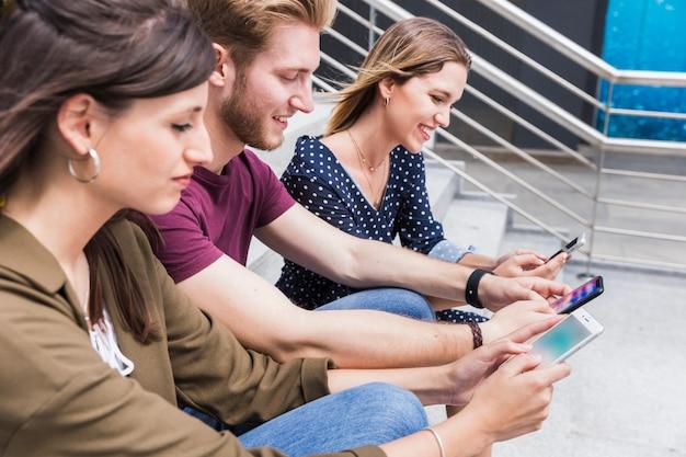 Grupo de amigos felizes, olhando para a tela do telefone móvel