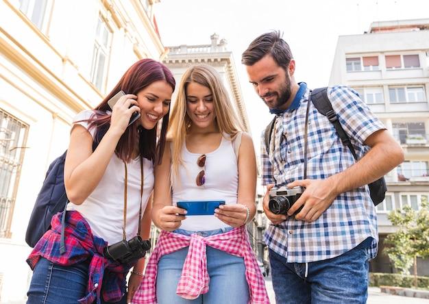Grupo de amigos felizes, olhando para o celular