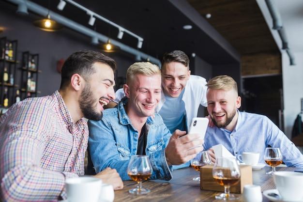 Grupo de amigos felizes olhando para smartphone sentado no restaurante