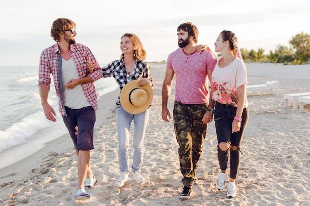 Grupo de amigos felizes passando momentos incríveis juntos e caminhando na praia ensolarada