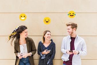 Grupo de amigos felizes que compartilham smiley emoji no celular