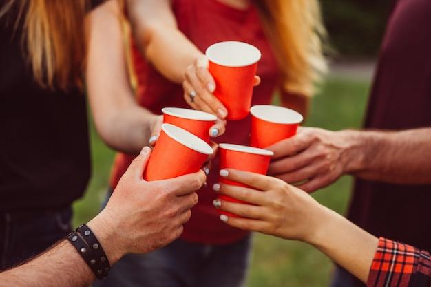 Grupo de amigos felizes relaxantes na natureza com vermelhos copos de álcool.