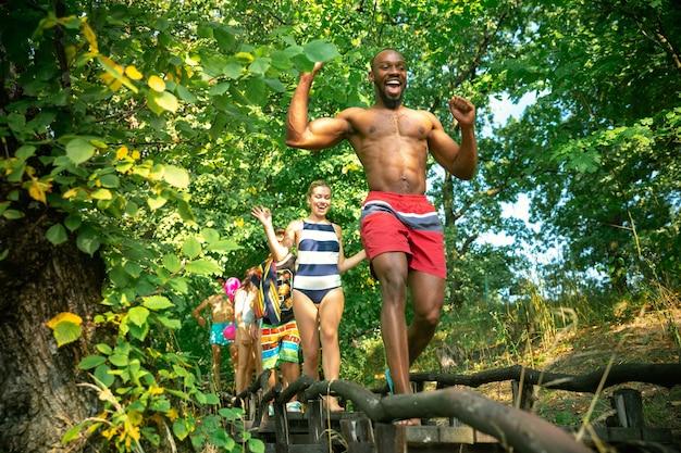 Grupo de amigos felizes, se divertindo enquanto corria para nadar no rio.