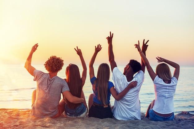 Grupo de amigos felizes se divertindo na praia ao amanhecer