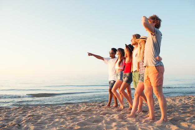 Grupo de amigos felizes se divertindo na praia do oceano