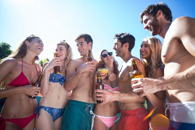 Grupo de amigos felizes segurando garrafas de cerveja e um copo de coquetel