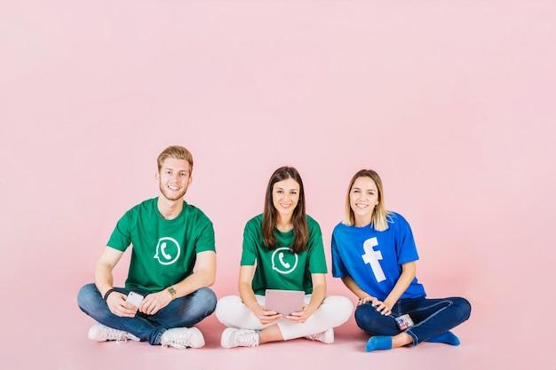 Grupo de amigos felizes, sentado no fundo rosa