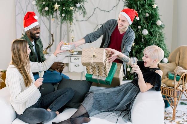 Grupo de amigos felizes, sentado no sofá branco e bebendo champanhe segurando os presentes de natal