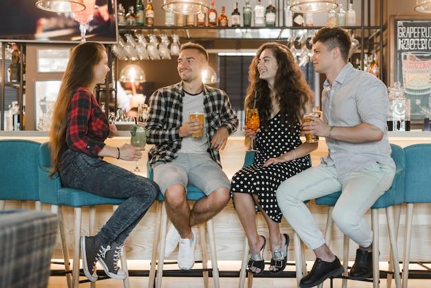 Grupo de amigos felizes sentados junto com bebidas no balcão de bar