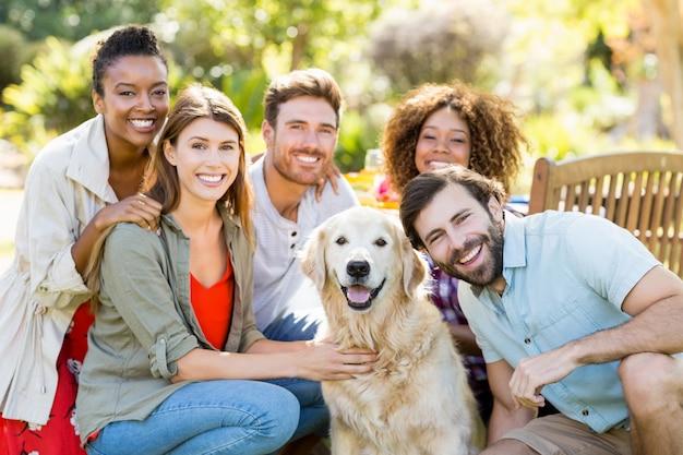 Grupo de amigos felizes sentados junto com o cachorro