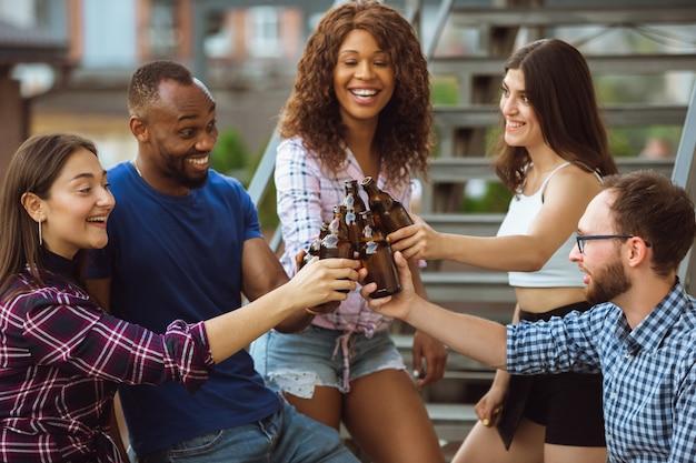 Grupo de amigos felizes, tendo a festa da cerveja em um dia ensolarado. descansando juntos ao ar livre, celebrando e relaxando, rindo. estilo de vida, conceito de amizade.