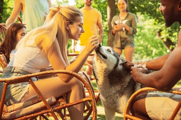 Grupo de amigos felizes, tendo uma festa de cerveja e churrasco em dia de sol. descansando juntos ao ar livre em uma clareira na floresta ou quintal. celebrando e relaxando, rindo. estilo de vida de verão, conceito de amizade.