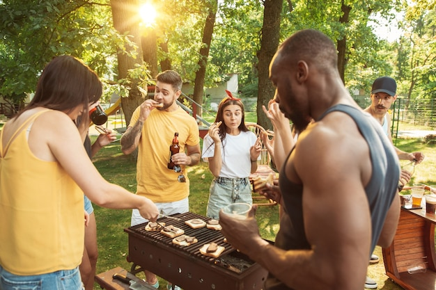 Grupo de amigos felizes, tendo uma festa de cerveja e churrasco em dia de sol. descansando juntos ao ar livre em uma clareira na floresta ou quintal