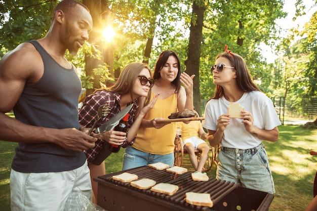 Grupo de amigos felizes, tendo uma festa de cerveja e churrasco em dia de sol.