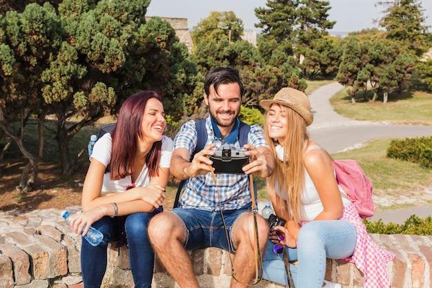 Grupo de amigos felizes tirando foto na câmera