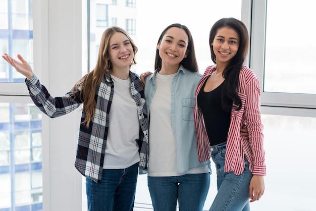 Grupo de amigos femininos multiétnicas abraçando