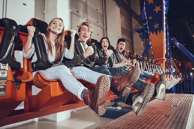 Grupo de amigos goza no lunapark. conceito de parque de diversões.