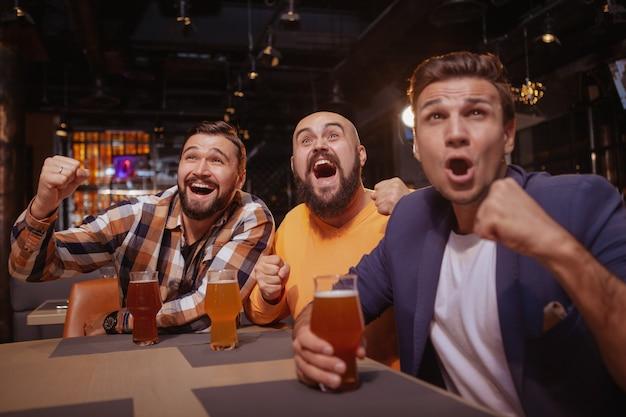 Grupo de amigos, gritando, assistindo jogo de futebol no bar da cerveja