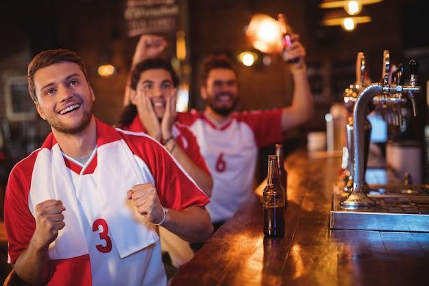 Grupo de amigos homens assistindo jogo de futebol