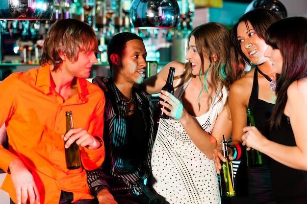 Grupo de amigos - homens e mulheres de diferentes etnias - se divertindo em uma discoteca ou boate