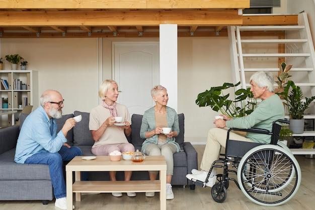 Grupo de amigos idosos conversando com um homem deficiente e bebendo chá juntos na sala de estar