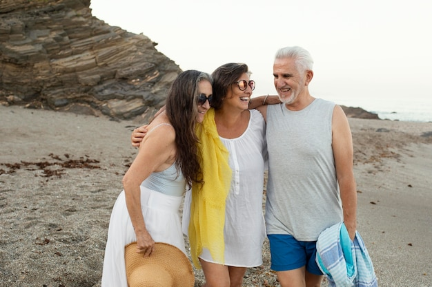 Grupo de amigos idosos passando um tempo juntos na praia