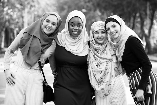 Grupo de amigos islâmicos abraçando e sorrindo juntos