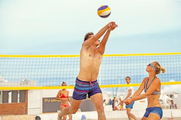 Grupo de amigos jogando bola na praia