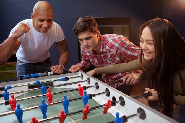 Grupo de amigos jogando futebol de mesa no bar de cerveja