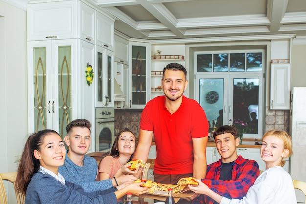 Grupo de amigos jovens felizes, à mesa da cozinha comendo pizza e outros pastéis em uma festa divertida