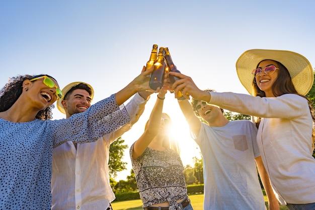 Grupo de amigos jovens hippie comemorando ao ar livre bebendo cerveja e brindando com garrafa