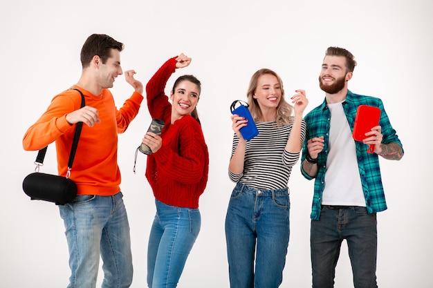 Grupo de amigos jovens hippie se divertindo juntos, sorrindo, ouvindo música em alto-falantes sem fio, dançando rindo na parede branca isolada com roupa colorida e elegante