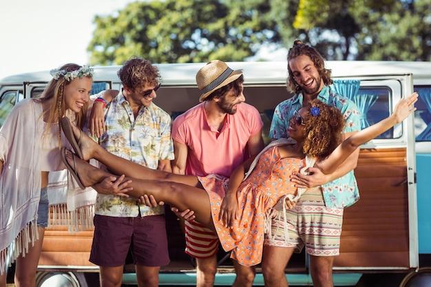 Grupo de amigos, levantando a mulher perto de caravana