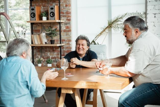 Grupo de amigos maduros felizes jogando cartas