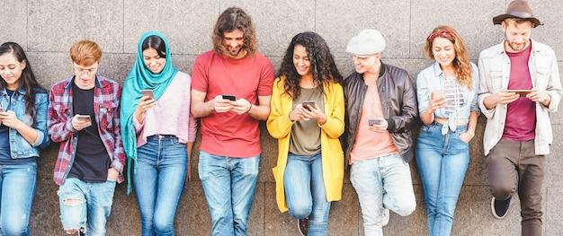 Grupo de amigos milenares, assistindo a história social em telefones móveis inteligentes. vício das pessoas em novas tendências tecnológicas