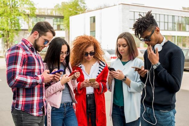 Grupo de amigos modernos usando o celular no exterior