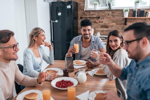 Grupo de amigos multi-étnicos que comem panquecas para o café da manhã e que têm o bom tempo em casa.