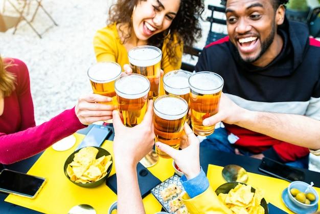 Grupo de amigos multiculturais bebendo e brindando cerveja em bar restaurante cervejaria