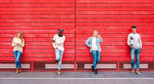 Grupo de amigos multiculturais usando smartphone por fundo de madeira vermelho