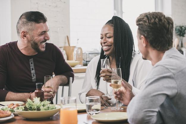 Grupo de amigos multiétnicas felizes que têm o partido de jantar em casa