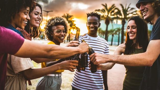 Grupo de amigos multiétnicos e felizes fazendo festa do lado de fora e comemorando brindando garrafas de cerveja no pôr do sol