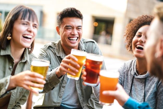 Grupo de amigos multiétnicos felizes bebendo e brindando cerveja em um restaurante-bar de cervejaria